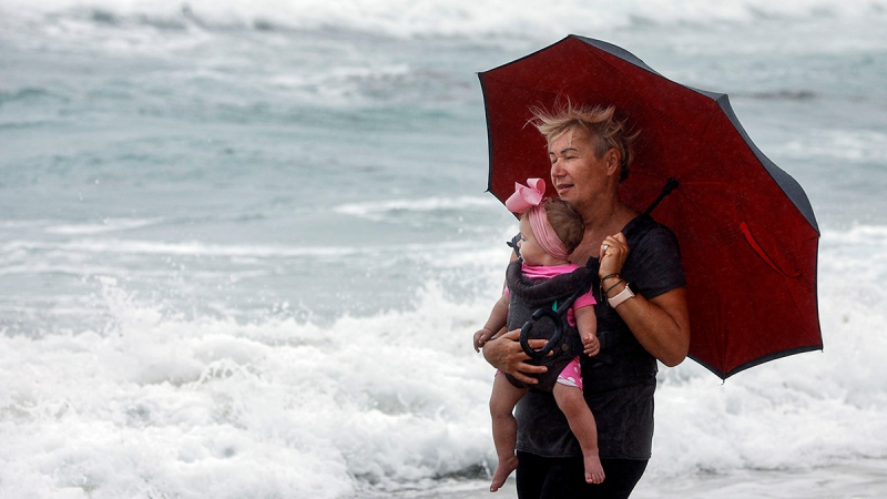 Joanna Janczak, a citizen of Poland, tries to stay dry at Lake Worth beach with 8 month-old Sophia in her arms as Isaias passes by Florida's east coast Sunday, Aug. 2, 2020. (Damon Higgins/The Palm Beach Post via AP)