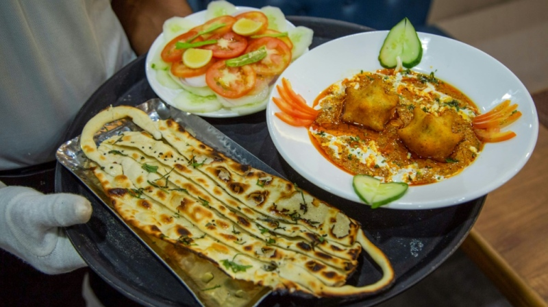A waiter carries 'COVID curry' and 'mask naan', two coronavirus-themed dishes, to customers at a restaurant in Jodhpur. (AFP)