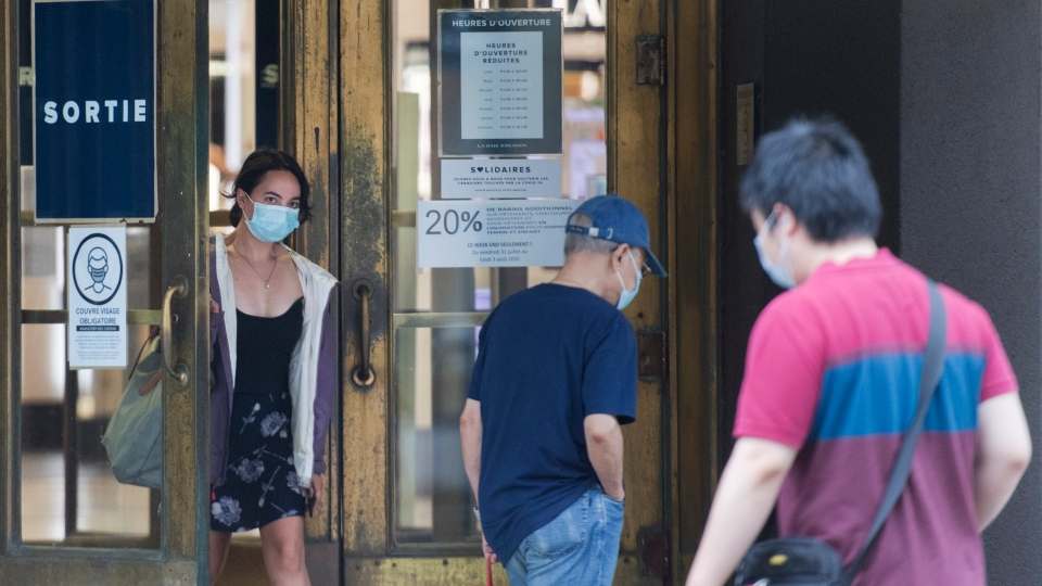 A woman wears a face mask as she exits a department store in Montreal, Sunday, August 2, 2020, as the COVID-19 pandemic continues in Canada and around the world. The Quebec government has made the wearing of masks and face coverings mandatory in all public spaces as of July 18 and will increase the number of people allowed to gather indoors and outdoors to 250 people as of August 3. THE CANADIAN PRESS/Graham Hughes