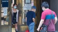 A woman wears a face mask as she exits a department store in Montreal, Sunday, August 2, 2020, as the COVID-19 pandemic continues in Canada and around the world. THE CANADIAN PRESS/Graham Hughes