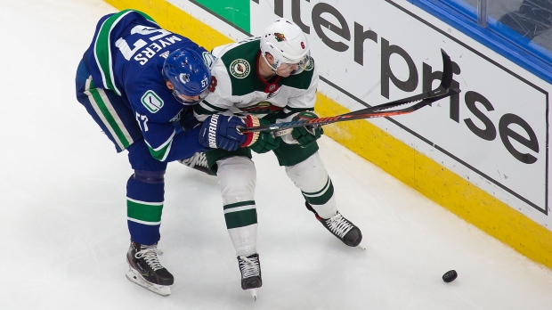 Vancouver Canucks' Tyler Myers (57) battles against Minnesota Wild's Ryan Donato (6) during third period NHL Stanley Cup qualifying round action in Edmonton, Sunday, Aug. 2, 2020. THE CANADIAN PRESS/Codie McLachlan