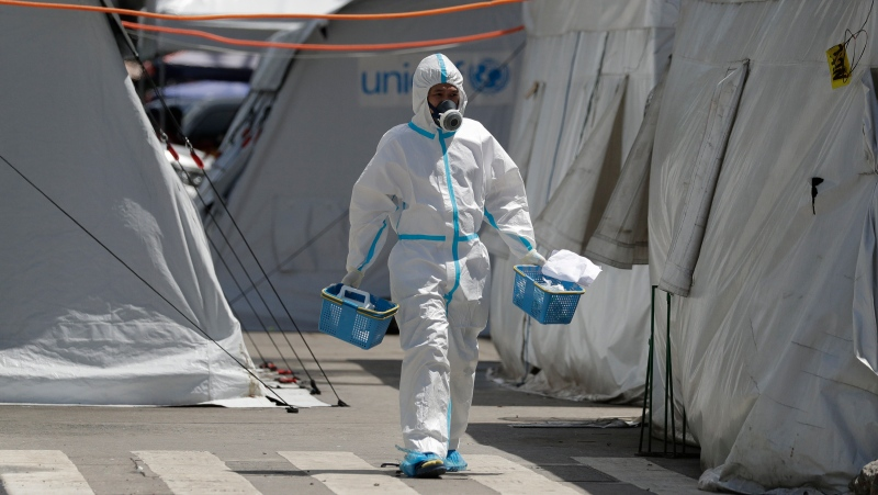 A health worker wearing protective suits walks in between tents at a parking lot that has been converted into an extension of the Gat Andres Bonifacio Memorial Medical Center in Manila, Philippines on Monday, Aug. 3, 2020. (AP Photo/Aaron Favila)