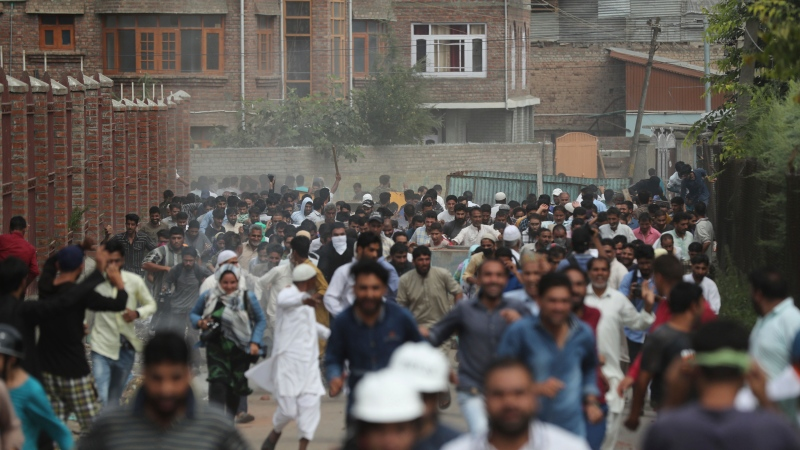 In this Aug. 30, 2019, file photo, Kashmiris protesting against Indian government stripping the Himalayan state's semi-autonomous powers run for cover as Indian police use tear gas and pellets to disperse them in Srinagar, Indian controlled Kashmir. (AP Photo/Mukhtar Khan, File)