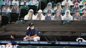 Seattle Mariners pitcher Yusei Kikuchi sits above the dugout near photos of fans during a baseball game against the Oakland Athletics, Monday, Aug. 3, 2020, in Seattle. (AP Photo/Ted S. Warren)