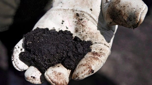An oil worker holds raw sand bitumen near Fort McMurray, Alta., on July 9, 2008. (Jeff McIntosh / THE CANADIAN PRESS)