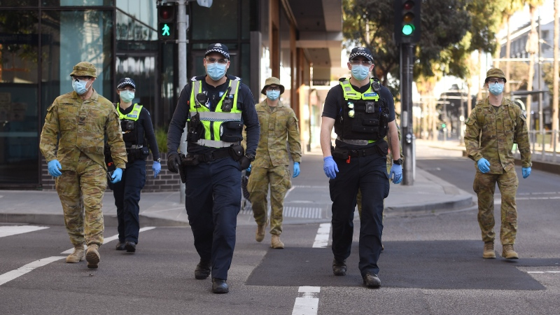 A group of police and soldiers patrol the Docklands area of Melbourne on August 2, 2020, after the announcement of new restrictions to curb the spread of the COVID-19 coronavirus. (WILLIAM WEST/AFP/Getty Images/CNN)