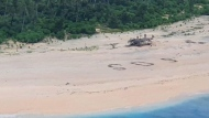 Three men rescued after writing 'SOS' in the sand