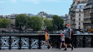 A family wearing face masks walk across the Notre Dame bridge in Paris, on July 28, 2020. (Kamil Zihnioglu / AP)
