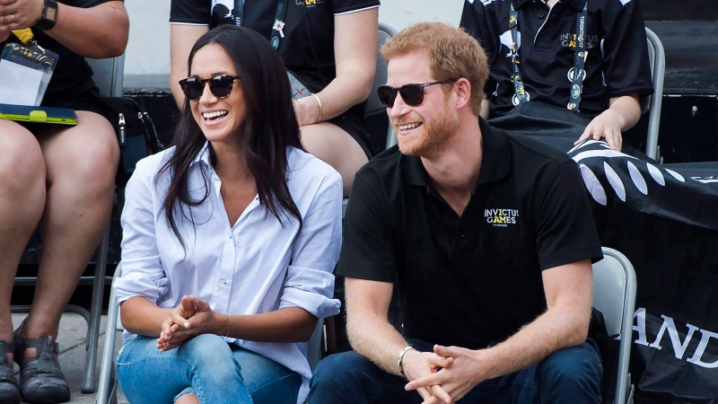 In this 2017 file photo, Harry and then-girlfriend Meghan laugh while watching the wheelchair tennis competition during the Invictus Games in Toronto on Monday, Sept. 25. It was the couple's first public appearance together. (THE CANADIAN PRESS/Nathan Denette)
