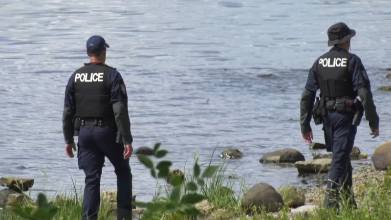 Ottawa police officers are seen along the shore of the Ottawa River near Bate Island during a search for the second of two men reported missing Friday night. The body of one man was recovered overnight. Aug. 1, 2020.