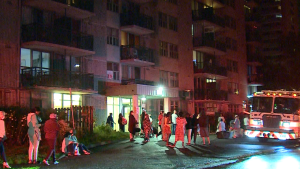 Residents of the high-rise building at 2651 Regina St. are seen outside after firefighters received several 911 calls  reporting smoke in several parts of the building at around 10:20 p.m. on Sunday, Aug. 2, 2020.