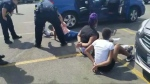 A Facebook video shows the children on the ground in a parking lot, surrounded by police. (Jenni Bennet/Facebook/CNN)