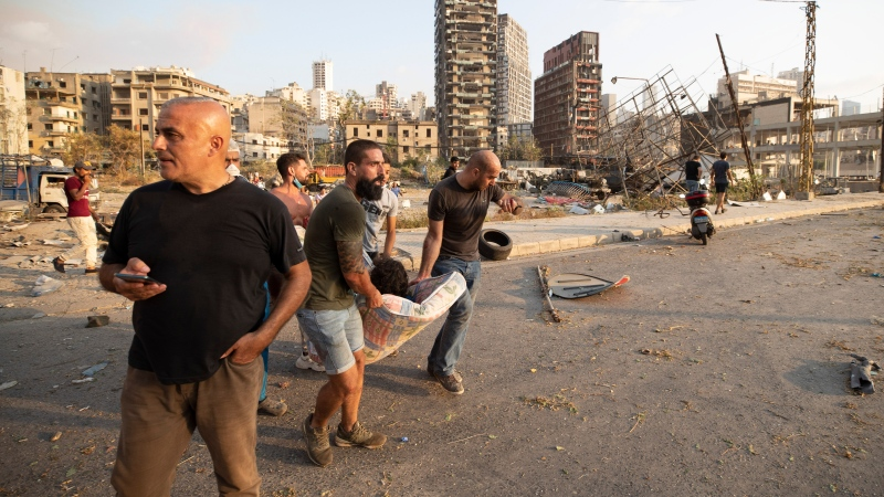 People carry a wounded after a massive explosion in Beirut, Lebanon, Tuesday, Aug. 4, 2020. Massive explosions rocked downtown Beirut on Tuesday, flattening much of the port, damaging buildings and blowing out windows and doors as a giant mushroom cloud rose above the capital. (AP Photo/Hassan Ammar)