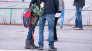 A boy hugs his father as he waits to be called to enter the schoolyard the Marie-Derome School in Saint-Jean-sur-Richelieu, Que. on Monday, May 11, 2020. Plans are being made across the country for how to safely send students back to school in the fall as the COVID-19 pandemic continues. THE CANADIAN PRESS/Paul Chiasson