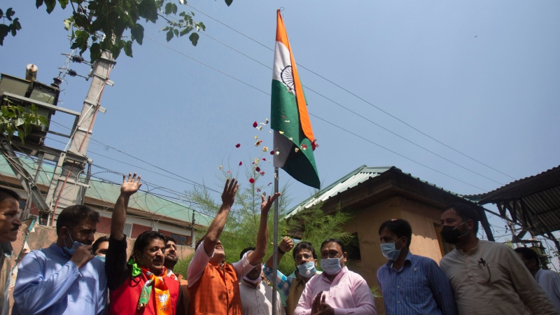 Kashmiri activists of India's ruling Bharatiya Janata Party (BJP) raise slogans after hoisting the national flag as they mark the first anniversary of India's decision to revoke the disputed region's semi-autonomy, in Srinagar, Indian controlled Kashmir, Wednesday, Aug. 5, 2020. (AP Photo/Mukhtar Khan)