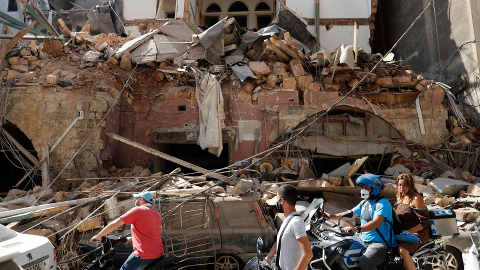 Citizens ride their scooters and motorcycles pass in front of a house that was destroyed in Tuesday's massive explosion in the seaport of Beirut, Lebanon, Wednesday, Aug. 5, 2020. (AP Photo/Hussein Malla)