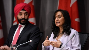 Minister of Public Services and Procurement Anita Anand speaks as Minister of Innovation, Science and Industry Navdeep Bains listens during a press conference on COVID-19 in West Block on Parliament Hill in Ottawa, on Friday, March 20, 2020. THE CANADIAN PRESS/Justin Tang