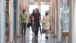 People wear face masks as they walk through the newly reopened Marche Bonsecours in Montreal, Sunday, August 2, 2020, as the COVID-19 pandemic continues in Canada and around the world. The Quebec government has made the wearing of masks and face coverings mandatory in all public spaces as of July 18 and increased the number of people allowed to gather indoors and outdoors to 250 people as of August 3.THE CANADIAN PRESS/Graham Hughes