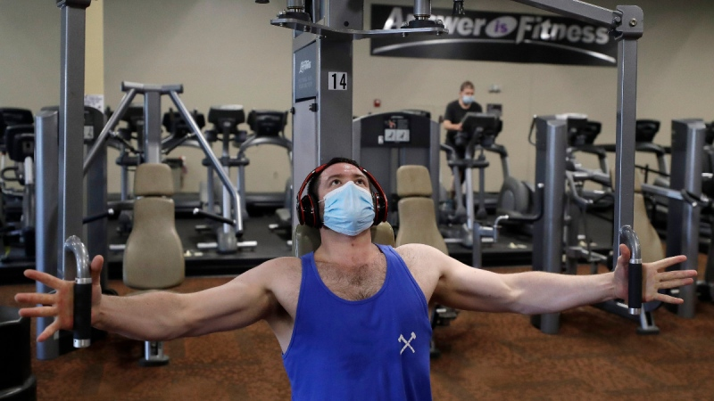 A customer at Answer is Fitness gym, who asked that his name not be used, works out on a piece of exercise equipment at a gym in Canton, Mass., on July 6, 2020. (Steven Senne / THE CANADIAN PRESS / AP)