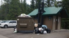 Garbage is seen piled around and on top of the bear-proof waste bin at Forget-Me-Not Pond in Kananaskis, Alta. on Aug. 3. (Supplied/Diane Peters)