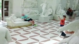 Security camera footage shows the man reclining next to the statue. (Source: Carabinieri Treviso / CNN)