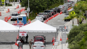 In this Sunday, July 12, 2020, vehicles wait in line at a COVID-19 testing site at the Miami Beach Convention Centre during the coronavirus pandemic in Miami Beach, Fla. As coronavirus cases surge in hard-hit Florida, so do the turnaround times for test results. (AP Photo/Lynne Sladky, File)