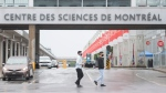 Two people wear face masks as they walk by the Montreal Science Centre in Montreal, Sunday, August 2, 2020. Governor General Julie Payette, who was chief operating officer at the science centre from 2013 to 2016, has been accused of creating a hostile workplace environment at Rideau Hall in the past week. THE CANADIAN PRESS/Graham Hughes