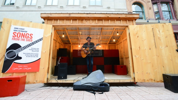 Ottawa musician Shawn Tavenier performs from behind a sheet of plexiglass during an outdoor performance on the Sparks Street Mall in Ottawa on Tuesday, Aug. 4, 2020. (Sean Kilpatrick/THE CANADIAN PRESS)