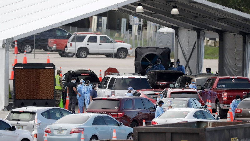 Healthcare workers conduct antigen testing, Wednesday, Aug. 5, 2020, at a COVID-19 testing site outside Hard Rock Stadium in Miami Gardens, Fla. State officials say Florida has surpassed 500,000 coronavirus cases. (AP Photo/Wilfredo Lee)