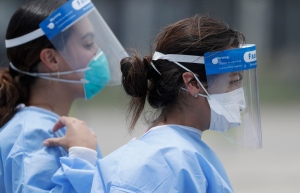 Healthcare workers walk to a tent, Wednesday, Aug. 5, 2020, at a COVID-19 testing site outside Hard Rock Stadium in Miami Gardens, Fla. (AP Photo/Wilfredo Lee)