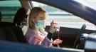 Woman wearing face mask in car using sanitizer