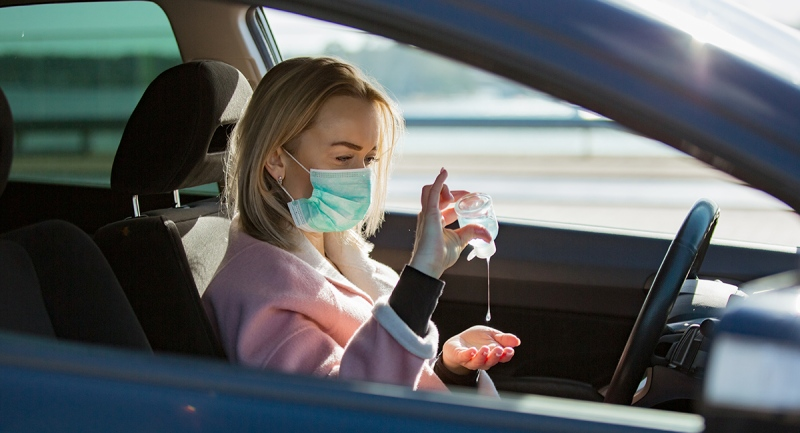 Woman wearing face mask in car using sanitizer