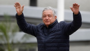 In this April 3, 2020 file photo, Mexican President Andres Manuel Lopez Obrador waves to supporters at the end of a visit to a Social Security Institute hospital that will be converted to receive patients infected with the new coronavirus, in the Coyoacan borough of Mexico City. (AP Photo/Rebecca Blackwell, File)