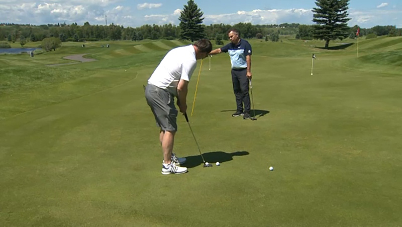 Glenn Campbell gets a tip on how to putt for dough from pro Scott Orban.