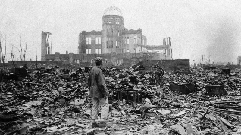 FILE - In this Sept. 8, 1945, file photo, an allied correspondent stands in a sea of rubble before the shell of a building that once was a movie theater in Hiroshima, western Japan, a month after the first atomic bomb ever used in warfare was dropped by the U.S. to hasten Japan's surrender. (AP Photo/Stanley Troutman, Pool, File)