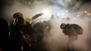 In this July 26, 2020, file photo, federal officers launch tear gas at demonstrators during a Black Lives Matter protest at the Mark O. Hatfield U.S. Courthouse in Portland, Ore. (AP Photo/Marcio Jose Sanchez, File)