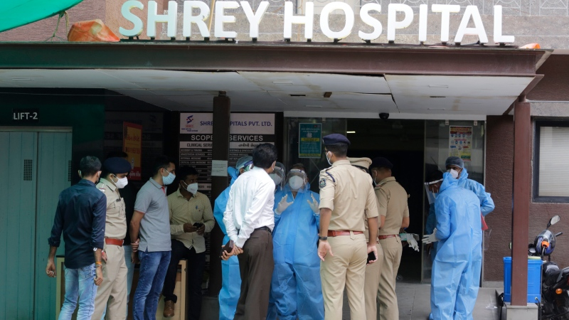 Forensic officers, wearing protective equipment, talk with police and government officers at Shrey hospital, where a fire broke out early morning in Ahmedabad, India, Thursday, Aug. 6, 2020. (AP Photo/Ajit Solanki)