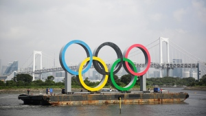 A symbol installed for the Olympic and Paralympic Games Tokyo 2020 on a barge is moved away from its usual spot by tugboats off the Odaiba Marine Park in Tokyo Thursday, Aug. 6, 2020. (AP Photo/Hiro Komae)