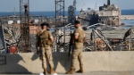 Lebanese army soldiers stand guard in front of destroyed ships at the scene where an explosion hit on Tuesday the seaport of Beirut, Lebanon, Thursday, Aug. 6, 2020. (AP Photo/Hussein Malla)