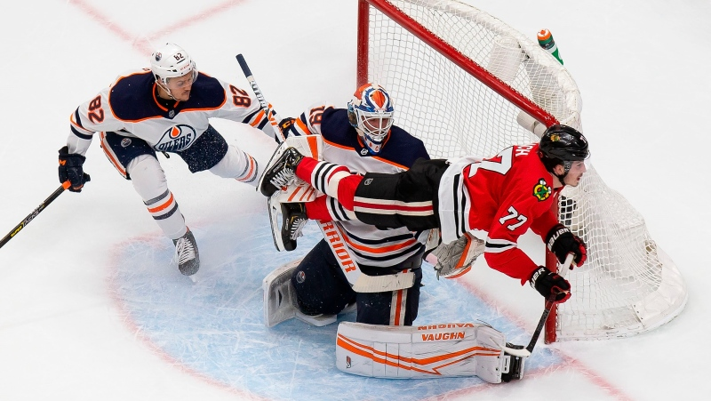 Chicago Blackhawks' Kirby Dach (77) flies past Edmonton Oilers' Caleb Jones (82) and goaltender Mikko Koskinen (19) during second period NHL Stanley Cup qualifying round action in Edmonton, Wednesday, Aug. 5, 2020. THE CANADIAN PRESS/Codie McLachlan