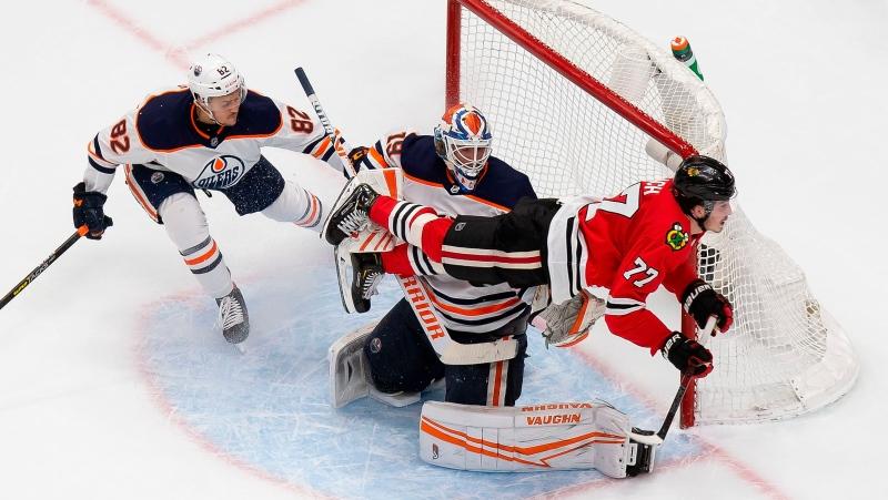 Chicago Blackhawks' Kirby Dach (77) flies past Edmonton Oilers' Caleb Jones (82) and goaltender Mikko Koskinen (19) during second period NHL Stanley Cup qualifying round action in Edmonton, Wednesday, Aug. 5, 2020. THE CANADIAN PRESS/Codie McLachlan
