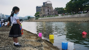 Saki Morioki, 5 years old, watches paper lanterns floating along the Motoyasu River in front of the Atomic Bomb Dome in Hiroshima, Japan, on Aug. 6, 2020. (Eugene Hoshiko / AP)