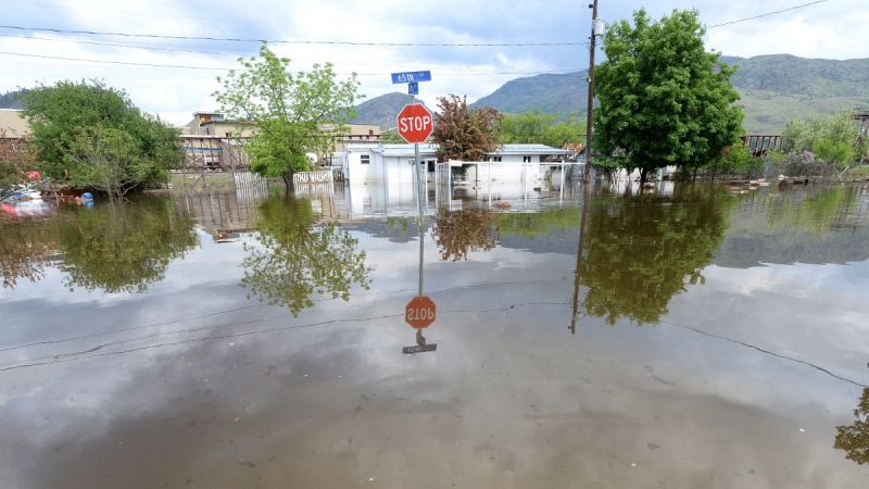 A stop sign is shown in a flooded intersection in Grand Forks, B.C., on May 17, 2018. (Jonathan Hayward / THE CANADIAN PRESS)