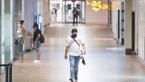 People wear face masks as they walk through a tunnel in a metro station in Montreal, Sunday, August 2, 2020, as the COVID-19 pandemic continues in Canada and around the world. The Quebec government has made the wearing of masks and face coverings mandatory in all public spaces as of July 18 and will increase the number of people allowed to gather indoors and outdoors to 250 people as of August 3.THE CANADIAN PRESS/Graham Hughes