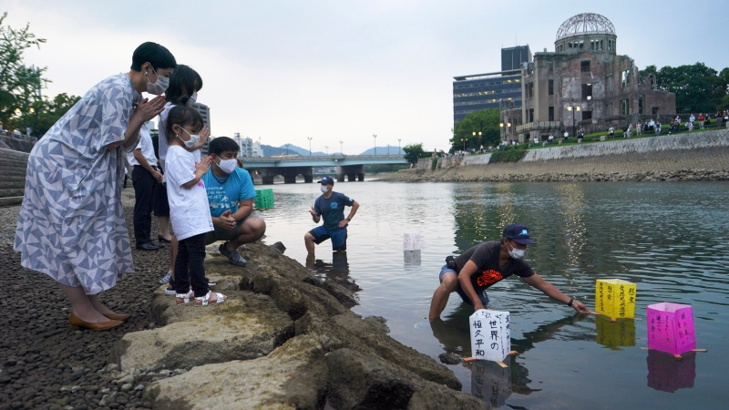 People pray as paper lanterns float along the Motoyasu River in front of the Atomic Bomb Dome, Thursday, Aug. 6, 2020. in Hiroshima, western Japan. Japan marked the 75th anniversary Thursday of the atomic bombing of Hiroshima. The official lantern event was cancelled to the public due to coronavirus but a small group of local representatives released some lanterns. (AP Photo/Eugene Hoshiko)