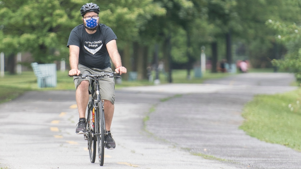 A man wears a face mask as he bikes in a park in Montreal, Sunday, August 2, 2020, as the COVID-19 pandemic continues in Canada and around the world. THE CANADIAN PRESS/Graham Hughes