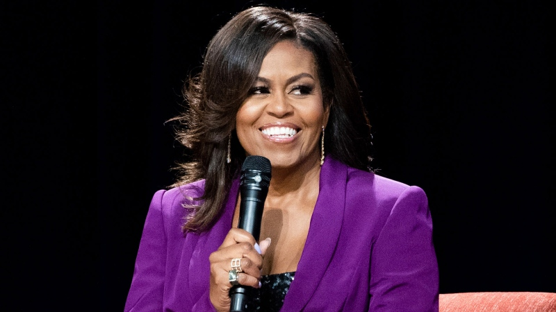 "This May 11, 2019 file photo shows former first lady Michelle Obama during ""Becoming: An Intimate Conversation with Michelle Obama,"" in Atlanta. The Obama's Higher Ground and Spotify announced Thursday that the former first lady will host ""The Michelle Obama Podcast"" on the streaming service. The podcast will debut exclusively on Spotify on July 29. (Photo by Paul R. Giunta/Invision/AP, File)"