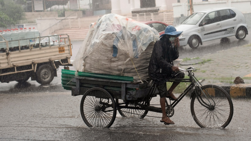 A man wearing a mask as a precaution against the coronavirus pedals his rickshaw during heavy rainfall in Kochi, Kerala state, India, Friday, Aug. 7, 2020. (AP Photo/R S Iyer)