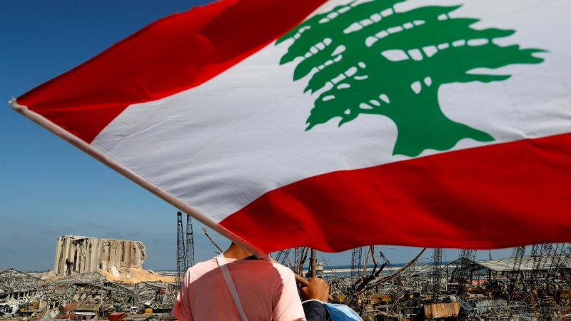 A man holds the Lebanese flag on Aug. 7, 2020, as he looks at the scene of the explosion that hit the seaport of Beirut, Lebanon. (Hussein Malla / AP)