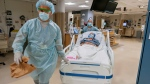 Members of the transplant anesthesiology team, Drs. Kamen V. Vlassalov, front, and Lindsay Wahl lead Carmen Blandin Tarleton to the operating room for her second face transplant, on July 28, 2020. (J. Kiely Jr. / Lightchaser Photography / Brigham and Women's Hospital, via AP)